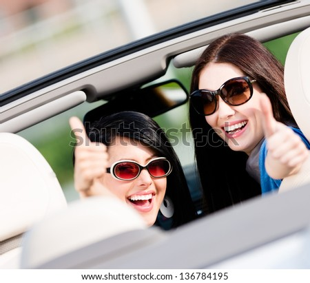 Two happy girls sitting in the car and thumbing up turn back and have fun while having little car trip - stock photo