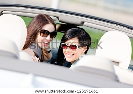 Two happy girls sitting in the car glance back and have fun while having little car trip - stock photo