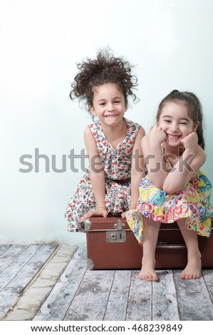 two happy girls sitting on a suitcase