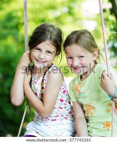 Two happy girls together on the swing - playing outdoor