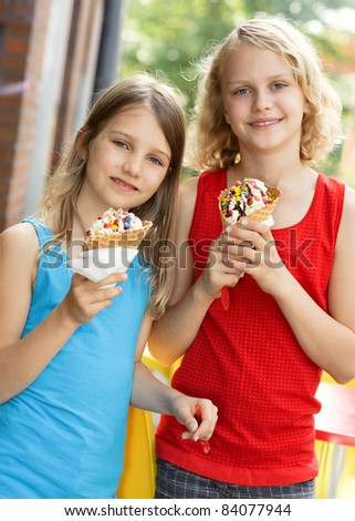 Two happy girls with ice cream cone in summer