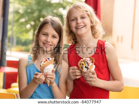 Two happy girls with ice cream cone in summer - stock photo