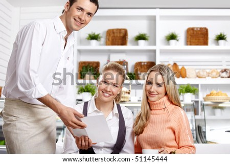Two happy girls with the waiter in cafe - stock photo