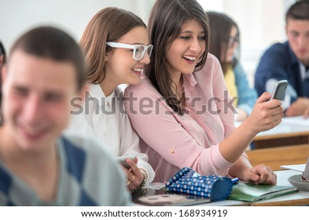 Two happy high school girls typing on mobile phone in classroom - stock photo