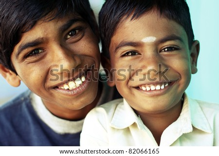 Two happy Indian boys posing to the camera.