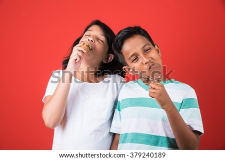 two happy indian kids and ice cream, two asian kids enjoying ice cream or cone or chocolate candy, girl and boy eating ice cream, isolated on red background - stock photo