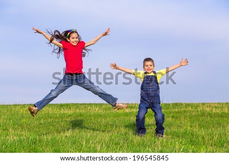 Two happy jumping kids on green field, outdoors