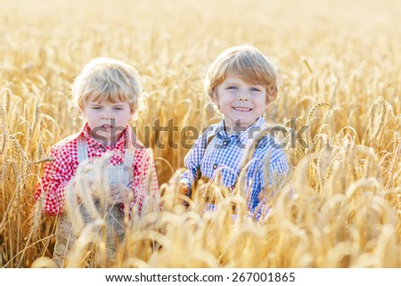 Two happy kid boys with blond hairs in yellow wheat field on warm summer day. - stock photo