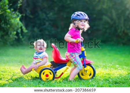 Two happy kids, adorable curly toddler girl and a funny cute baby boy, brother and sister, playing together riding a bike, first colorful tricycle, having fun in the garden on a sunny summer day - stock photo