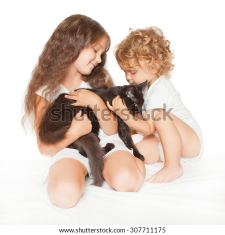 Two happy kids, child and baby playing with Maine Coon kitten. Isolated on white background. - stock photo