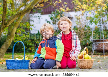Two happy kids eating apples in home's garden, outdoors. Own harvest. Children in colorful rubber boots on autumn day. - stock photo