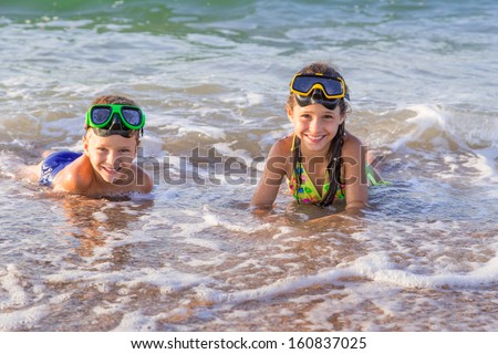 Two happy kids in diving masks swim in the surf