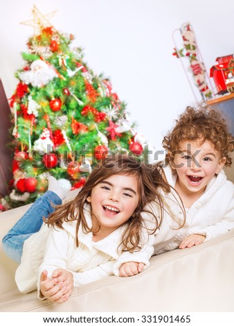 Two happy kids lying down on sofa near beautiful decorated Christmas tree and laughing, cheerful family spending winter holidays at home - stock photo