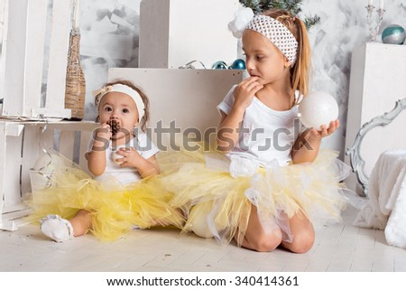 Two happy kids lying down on sofa under beautiful decorated Christmas tree and laughing, cheerful family spending winter holidays at home - stock photo
