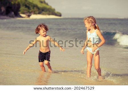 two happy kids playing on beach at the day time - stock photo