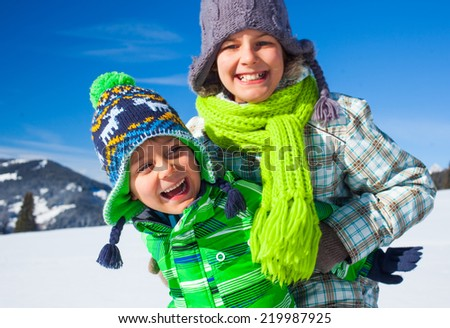 Two happy kids playing winter on the snow in Alps - stock photo