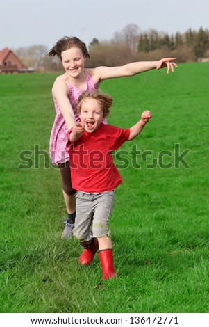 Two happy kids running on a green meadow