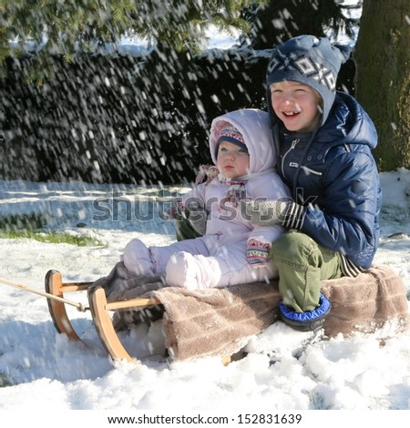 Two happy kids, teenager boy with baby sister enjoying snow sitting on sledge - stock photo