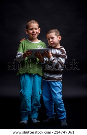 Two happy kids using touch pad computer and isolated on black - stock photo