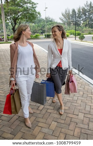 Two Happy Ladies Carrying Paper Bags in City