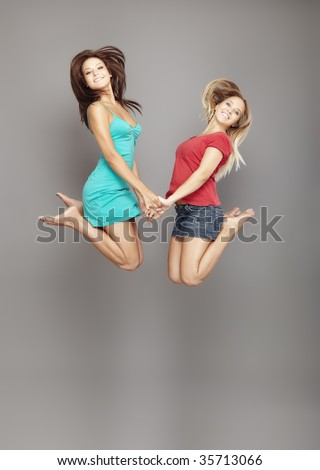 Two happy ladies jumping on a gray background