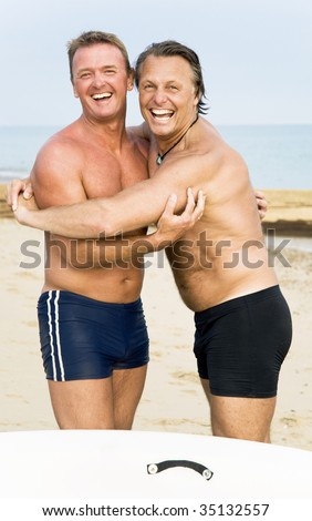 Two happy laughing gay men are hugging on the beach. - stock photo