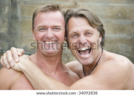 Two happy laughing gay men cuddle up together. - stock photo