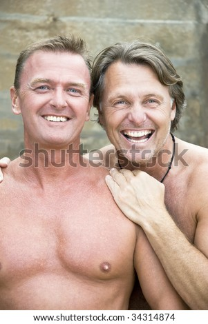 Two happy laughing gay men in their forties. - stock photo