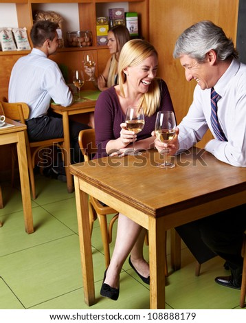 Two happy laughing senior people drinking white wine in restaurant