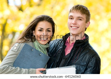 Two Happy laughing young students in autumn outdoors over yellow leaves
