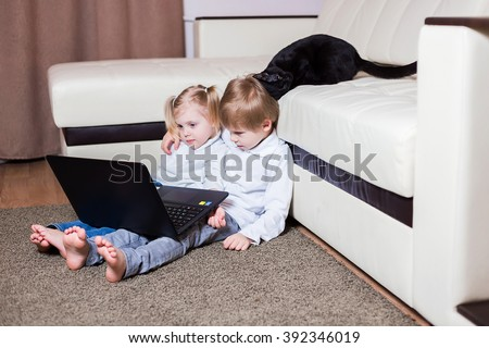 two happy little baby boy and a fair-skinned blonde girl (brother and sister) sitting on the floor with a laptop and watching cartoons on the computer, a cat on a sofa ironed (fins) on kid