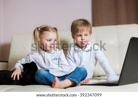 two happy little baby boy and a fair-skinned blonde girl (brother and sister) sitting on the floor with a laptop, looking at the picture and smile - stock photo