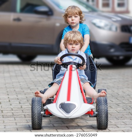 Two happy little boy friends having fun with toy race car in summer garden, outdoors. Active kid pushing the car with younger boy. Outdoor games for children in summer concept. - stock photo