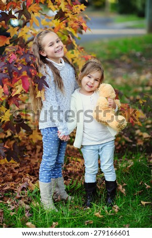 Two happy little girl playing at autumn day outdoor - stock photo