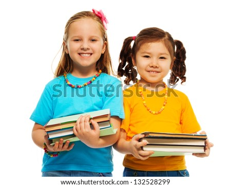 Two happy little girls Asian and Caucasian black and light haired with stack books standing isolated on white - stock photo