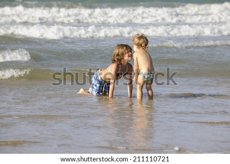 Two happy little girls having fun on the beach. - stock photo