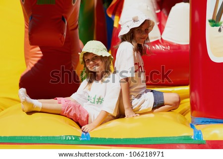 Two happy little girls kids playing in inflatable bouncing castle playground.Pretty small white female models in sun hats.Bright sunny summer day,smiling friendly girls sisters.