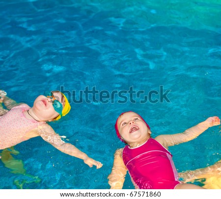 Two happy little girls learning to swim in a pool - stock photo