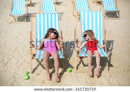 Two happy little girls lie on sun loungers and look at each other on beach at sunny day. - stock photo