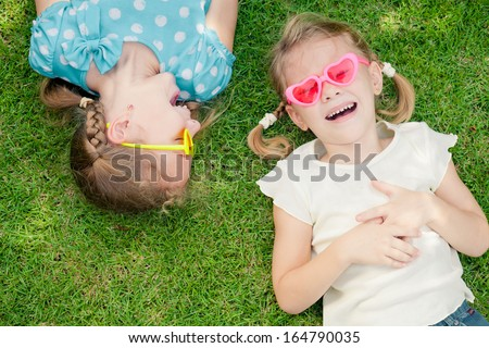 two happy little girls playing in the park in the day time - stock photo