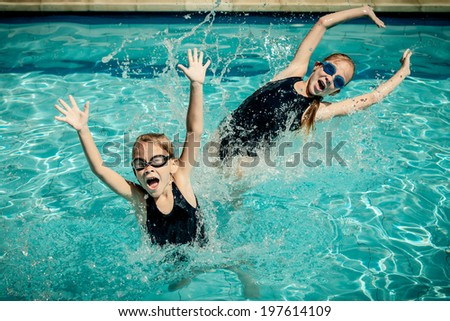 two happy little girls playing  in the swimming pool - stock photo