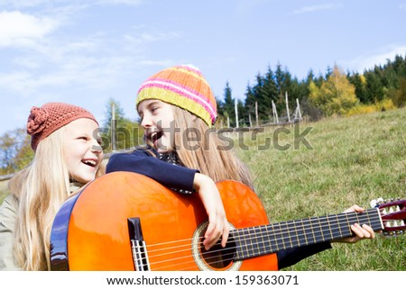 Two happy little girls singing and playing a guitar - stock photo