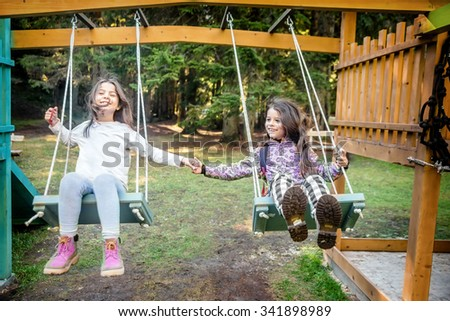 Two happy little girls swinging on the swing in a children playground - stock photo