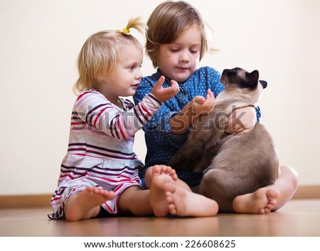 Two happy little girls  with cat sitting on the floor - stock photo