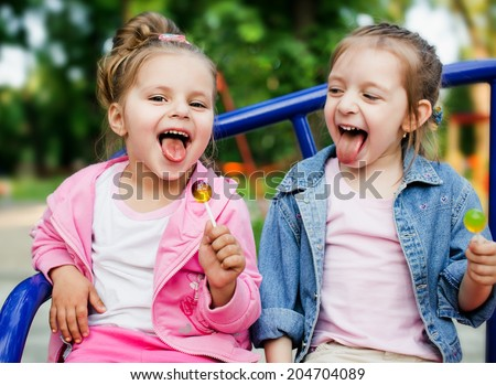two happy little girls with lollipops outdoors - stock photo