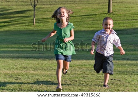 Two happy little kids having fun while running through the grassy field and racing against each other. - stock photo