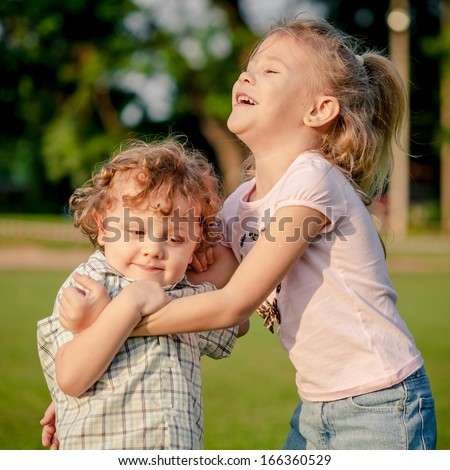 two happy little kids playing in the park in the day time