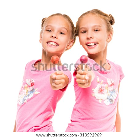 Two happy little sisters with lollipops, on white background. - stock photo