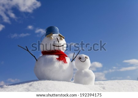 Two happy looking snowmen in the outdoors, one bigger than the other. - stock photo