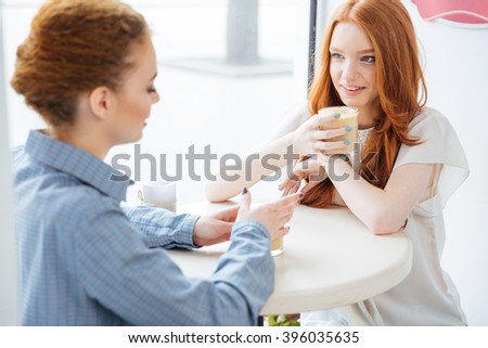 Two happy lovely young women talking and drinking coffee in cafe - stock photo